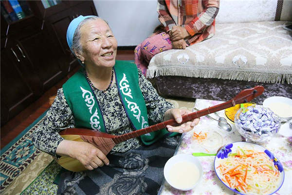 Jamalhan·Harbat performs Aken songs in her home in Emin county, Tacheng prefecture, Xinjiang Uygur autonomous region, May 24, 2016. (Photo by Gaoyuan Lingzi/provided to chinadaily.com.cn)
